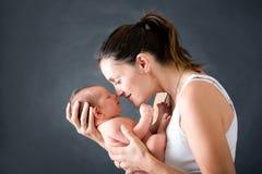 Potomstwa matkują, całujący jej nowonarodzonej chłopiec i ściskający Fotografia Stock