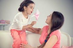 Potomstwa matkują i mała śliczna córka bawić się z pinwheel obrazy stock