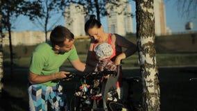 Potomstwa matkują i ojciec piękna chłopiec siedzi puszek w krześle w bicyklu parku zbiory