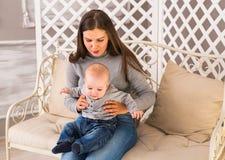 Potomstwa matkują kobiety przytulenia w ona i mienia ręki dziecka dziecka dzieciaka chłopiec smilling śmiać się Fotografia Stock