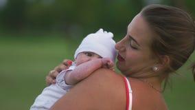 Potomstwa matkują mienia i bawić się z jej chłopiec dzieckiem jest ubranym jaskrawą czerwieni suknię w miasto parka pozycji - syn zbiory wideo