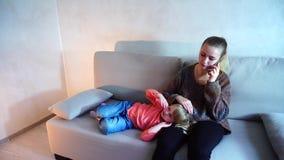 Potomstwa matkują obsiadanie na leżance w żywym pokoju, mali córek kłamstwa na kobiet kolanach zdjęcie wideo