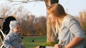 Potomstwa matkują obsiadanie na trawie opowiada i bawić się z jej małym dzieckiem, klaskać rękami sunlight zbiory wideo