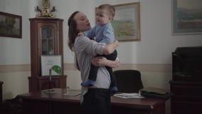 Potomstwa matkuj? pozycj? w nowo?ytnym biurowym pokoju w ona domowy mienia dziecka syn w r?kach Dziecko jest niegrzeczny, obraca  zbiory wideo
