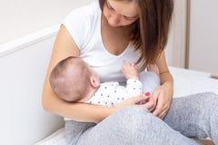 Potomstwa matkują trzymać jej dziecka i breastfeeding on fotografia stock