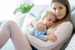 Potomstwa matkują, trzymający jej chorej berbeć chłopiec, ściska on w domu obraz stock