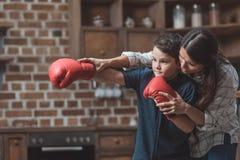 Potomstwa matkują uczyć jej małego syna w bokserskich rękawiczkach dlaczego boksować fotografia royalty free