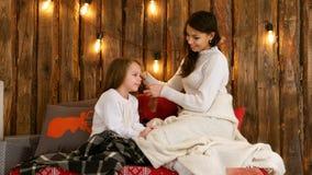 Potomstwa matkują w białym pulowerze plesie jej córka włosy Zdjęcie Stock