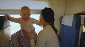 Potomstwa matkują z dzieckiem podróżuje pociągiem w ona ręki zbiory wideo