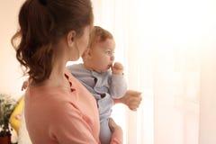 Potomstwa matkują z jej ślicznym małym dzieckiem blisko okno Fotografia Stock