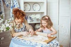 Potomstwa matkują z jej małą córką gotują Obrazy Royalty Free