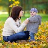 Potomstwa matkują z jej małym dzieckiem ma zabawę Obrazy Stock