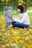 Potomstwa matkują z jej małym dzieckiem w jesień parku Obraz Stock