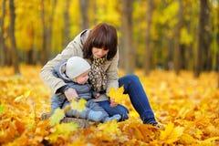 Potomstwa matkują z jej małym dzieckiem w jesień parku Zdjęcia Stock