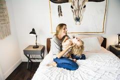 Potomstwa matkują z jej małym synem relaksuje w weekend i bawić się w łóżku wpólnie zdjęcie stock