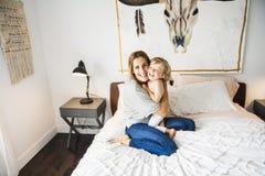 Potomstwa matkują z jej małym synem relaksuje w weekend i bawić się w łóżku wpólnie zdjęcia royalty free