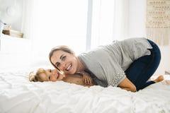 Potomstwa matkują z jej małym synem relaksuje w weekend i bawić się w łóżku wpólnie zdjęcia stock