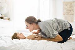 Potomstwa matkują z jej małym synem relaksuje w weekend i bawić się w łóżku wpólnie obraz stock
