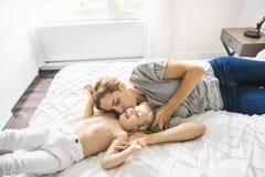 Potomstwa matkują z jej małym synem relaksuje w weekend i bawić się w łóżku wpólnie zdjęcie royalty free