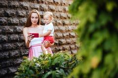 Potomstwa matkują z jej małym synem w mieście fotografia stock