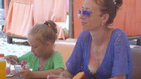 Potomstwa matkują z małą śliczną córką siedzą przy seaview kawiarnią zbiory