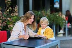 Potomstwa matkują z małą córką ma posiłek w outdoors kawiarni fotografia stock