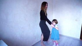 Potomstwa matkują z małą córką wpólnie tanczą w domowym pokoju w dniu i zdjęcie wideo