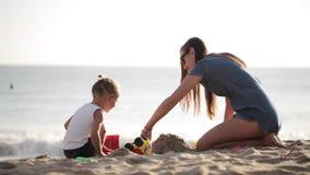 Potomstwa matkują z małym doughter bawić się z piaskiem na plaży zdjęcie wideo