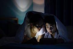 Potomstwa matkują z synem bawić się z smartphone na łóżku Zdjęcia Royalty Free