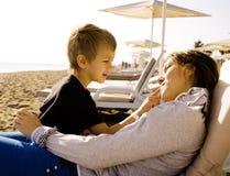 Potomstwa matkują z synem odpoczywa na dennym wybrzeżu, szczęśliwy rodzinny togethe Obraz Stock