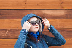 Potomstwa Modelują PosGirl w niebieskiej marynarce z kapiszonem, okulary przeciwsłoneczni, drewniany tło, patrzeją popierać kogoś obrazy royalty free