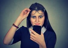 Potomstwa niepokoją zmieszanej kobiety patrzeje telefon komórkowego z szkłami Fotografia Stock