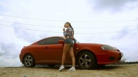 Potomstwa odchudzają damy pozuje przez czerwonego sportowego samochód i liźnięcia lizak zbiory