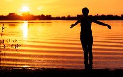 Potomstwa odchudzają kobiety medytuje na bankach jezioro przy zmierzchem Obraz Stock