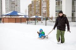 Potomstwa ojciec i chłopiec cieszy się sanie przejażdżkę Dziecka sledding Berbecia dzieciaka jazdy saneczki Dziecko sztuka outdoo Obrazy Royalty Free