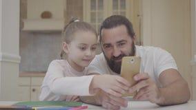 Potomstwa ojcują i jego mała śliczna córka siedzi w żywym pokoju rysować z i gmeraniu na smartphone obrazku zbiory wideo