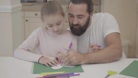 Potomstwa ojcują i jego mała śliczna córka siedzi w żywym pokoju i rysunku z markierami pocztówkowymi na zielonym kartonie zdjęcie wideo