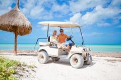 Potomstwa ojcują i dwa małego dziecka jedzie golfową furę na tropikalnej plaży Fotografia Stock