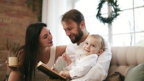 Potomstwa ojcują i jego syn czytelnicza książka, podczas gdy matka pije herbaty i całuje jej męża Rodzinni czytelniczy boże narod zdjęcie wideo