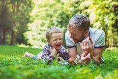 Potomstwa ojcują i jego syna łasowania truskawki w parku piknik na terenach odkrytych portret Obrazy Royalty Free