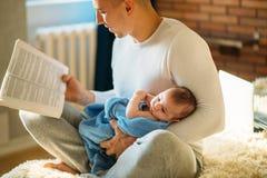 Potomstwa ojcują mały dziecko i czytelnicza książka Obrazy Stock