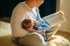 Potomstwa ojcują mały dziecko i czytelnicza książka Zdjęcia Royalty Free