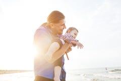 Potomstwa ojcują trzymać jego dziecka na plażowym wpólnie mieć zabawę Zdjęcie Royalty Free