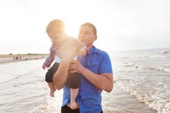 Potomstwa ojcują trzymać jego dziecka na plażowym wpólnie mieć zabawę Zdjęcie Stock