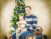 Potomstwa ojcują z śmieszną chłopiec blisko nowy rok jodły ilustracyjny lelui czerwieni stylu rocznik Zdjęcie Stock