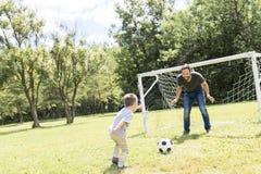 Potomstwa ojcują z jego małym synem bawić się futbol na futbolowej smole Obraz Royalty Free