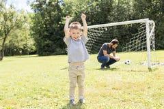 Potomstwa ojcują z jego małym synem bawić się futbol na futbolowej smole Fotografia Stock