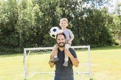 Potomstwa ojcują z jego małym synem bawić się futbol na futbolowej smole Zdjęcie Stock
