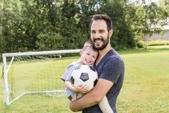 Potomstwa ojcują z jego małym synem bawić się futbol na futbolowej smole Obrazy Stock