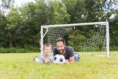 Potomstwa ojcują z jego małym synem bawić się futbol na futbolowej smole Zdjęcia Royalty Free